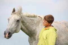 Muchacho feliz del adolescente y caballo blanco en el campo Fotos de archivo libres de regalías