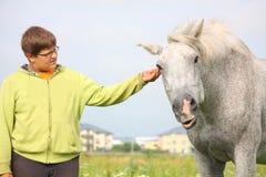 Muchacho feliz del adolescente y caballo blanco en el campo Imágenes de archivo libres de regalías