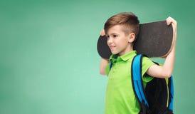 Muchacho feliz del estudiante con la mochila y el monopatín Fotos de archivo libres de regalías