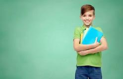 Muchacho feliz del estudiante con las carpetas y los cuadernos Imagen de archivo libre de regalías