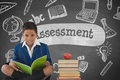 Muchacho feliz del estudiante en la lectura de la tabla contra la pizarra gris con el texto de la evaluación y educación y sc fotografía de archivo libre de regalías