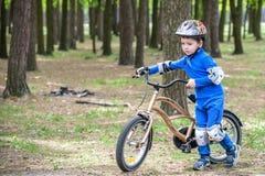 Muchacho feliz del niño de 4 años que se divierten en bosque del otoño con una bicicleta en día hermoso de la caída Niño activo q Fotos de archivo libres de regalías