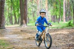 Muchacho feliz del niño de 4 años que se divierten en bosque del otoño o del verano con una bicicleta en día de primavera hermoso Fotos de archivo