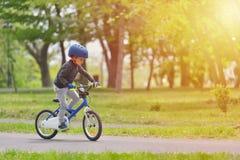 Muchacho feliz del niño de 5 años que se divierten en parque de la primavera con una bicicleta en día hermoso de la caída Casco d fotos de archivo