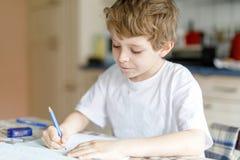 Muchacho feliz del niño de la escuela en casa que hace la preparación Foto de archivo