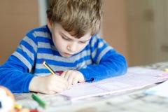 Muchacho feliz del niño de la escuela en casa que hace la preparación Fotografía de archivo