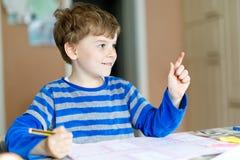Muchacho feliz del niño de la escuela en casa que hace la preparación Imagen de archivo libre de regalías