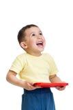 Muchacho feliz del niño que juega con la tableta de la PC que mira para arriba Imagen de archivo libre de regalías