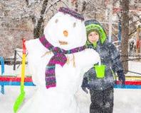 Muchacho feliz del niño que juega con un muñeco de nieve en paseo del invierno en naturaleza Niño que se divierte en el tiempo de Fotos de archivo libres de regalías