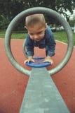 Muchacho feliz del niño que juega seesawing en patio en el parque filtrado Imagen de archivo