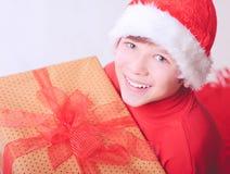 Muchacho feliz del niño que lleva el sombrero de santa con los presentes Imágenes de archivo libres de regalías