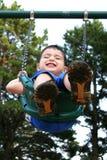 Muchacho feliz del niño que ríe en el oscilación Imagenes de archivo
