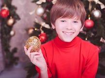Muchacho feliz del niño que sostiene la bola de la Navidad Foto de archivo libre de regalías