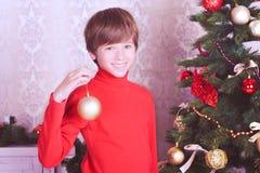 Muchacho feliz del niño que sostiene la bola de la Navidad Imagen de archivo libre de regalías