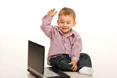 Muchacho feliz del niño que usa la computadora portátil Imágenes de archivo libres de regalías