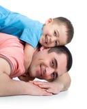 Muchacho feliz del niño y su papá que mienten en el piso Fotos de archivo