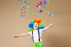 Muchacho feliz del payaso con la peluca colorida grande ¡Deje el partido del ` s! Niño divertido Fotografía de archivo