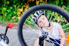 Muchacho feliz del pequeño niño en el casco blanco que repara su bicicleta foto de archivo