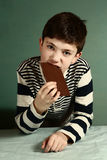 Muchacho feliz del preadolescente con la barra de chocolate Imagen de archivo