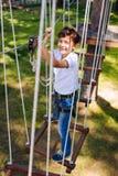Muchacho feliz del preadolescente que se coloca en el oscilación en el parque de la cuerda Foto de archivo