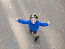 Muchacho feliz emocionado sobre patinaje sobre ruedas imagenes de archivo