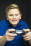 Muchacho feliz en azul con el regulador del juego Foto de archivo libre de regalías