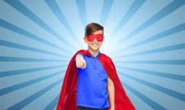 Muchacho feliz en cabo y máscara rojos del super héroe Fotos de archivo