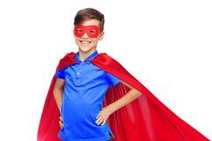 Muchacho feliz en cabo y máscara rojos del super héroe Foto de archivo libre de regalías
