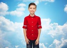 Muchacho feliz en camisa roja sobre el cielo azul Fotografía de archivo