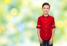 Muchacho feliz en camisa roja sobre luces verdes Imagen de archivo