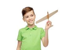 Muchacho feliz en camiseta verde del polo con el aeroplano del juguete Imagen de archivo libre de regalías