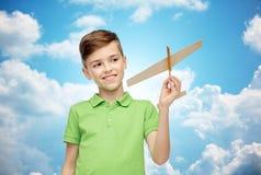 Muchacho feliz en camiseta verde del polo con el aeroplano del juguete Fotografía de archivo