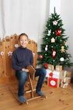 Muchacho feliz en el caballo de madera cerca del árbol de navidad Fotos de archivo