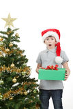 Muchacho feliz en el sombrero de santa sorprendido por el regalo de Navidad Fotografía de archivo
