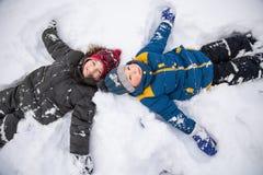 Muchacho feliz en juego de la nieve y día soleado de la sonrisa al aire libre Imagen de archivo libre de regalías