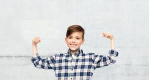 Muchacho feliz en la camisa a cuadros que muestra los puños fuertes Foto de archivo
