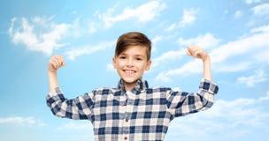 Muchacho feliz en la camisa a cuadros que muestra los puños fuertes Imagen de archivo libre de regalías
