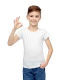 Muchacho feliz en la camiseta blanca que muestra la muestra aceptable de la mano Imagenes de archivo
