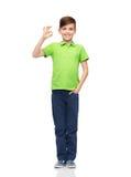 Muchacho feliz en la camiseta blanca que muestra la muestra aceptable de la mano Imágenes de archivo libres de regalías