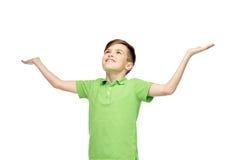 Muchacho feliz en la camiseta del polo que aumenta las manos para arriba Fotografía de archivo