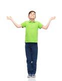 Muchacho feliz en la camiseta del polo que aumenta las manos para arriba Foto de archivo libre de regalías