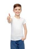 Muchacho feliz en la camiseta en blanco blanca que muestra los pulgares para arriba Fotos de archivo