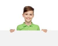 Muchacho feliz en la camiseta que lleva a cabo al tablero en blanco blanco Foto de archivo libre de regalías