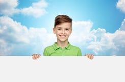 Muchacho feliz en la camiseta que lleva a cabo al tablero en blanco blanco Imagenes de archivo