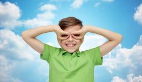 Muchacho feliz en la camiseta que se divierte y que hace caras Imagen de archivo libre de regalías