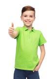 Muchacho feliz en la camiseta verde del polo que muestra los pulgares para arriba Imagenes de archivo