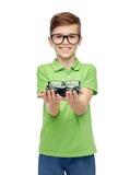 Muchacho feliz en la camiseta verde del polo que sostiene las lentes Imagen de archivo libre de regalías
