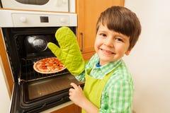 Muchacho feliz en la manopla que sale la pizza caliente del horno fotografía de archivo libre de regalías