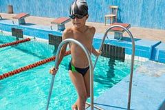 Muchacho feliz en la piscina que se coloca en el borde Foto de archivo libre de regalías