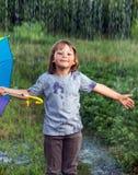 Muchacho feliz en lluvia Imagenes de archivo